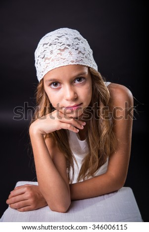 Young girl with long hair and cap on black background - stock photo