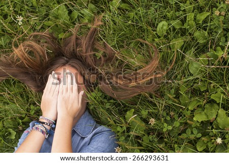 Young girl with long hair, closing eyes while lying in the green grass. - stock photo