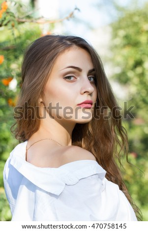 Young girl with long hair in the park on a background of mountain ash