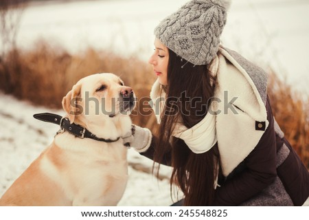 Young girl with love looking at your dog. Winter portrait. - stock photo