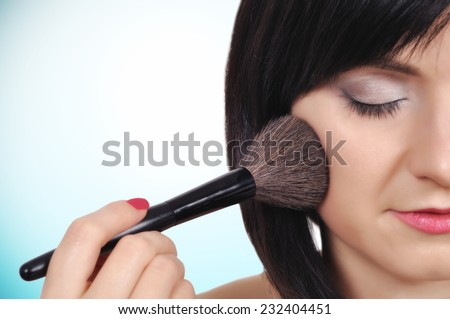 young girl with makeup brush, close up - stock photo