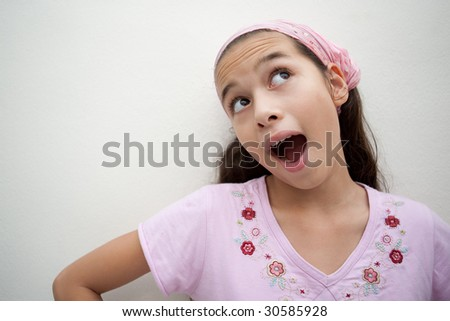 Young girl with mouth open as if struck with a good idea - stock photo