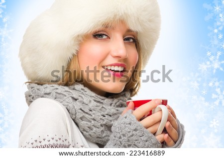 Young girl with mug on blue winter background - stock photo