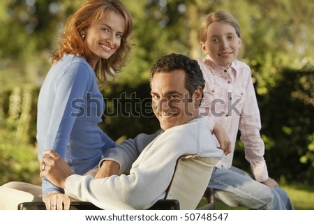 Young girl with parents in back yard, portrait