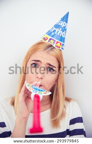 Young girl with party hat and blows whistle over gray background. Looking at camera - stock photo