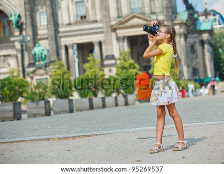 young girl with photo camera on Cathedral in Berlin background