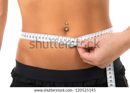 Young girl with piercing girl measuring her body for a perfect shape - stock photo