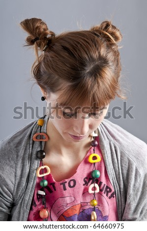 Young girl with pigtails, and colorful necklace laying and writes with a pen