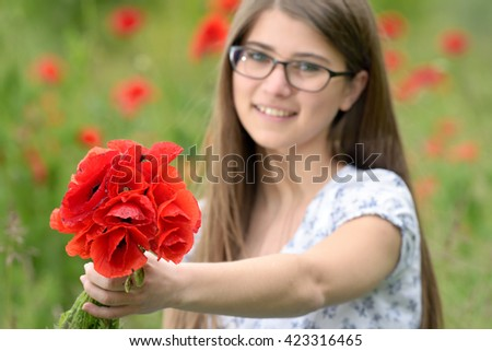 Young girl with poppy bouquet on field - stock photo