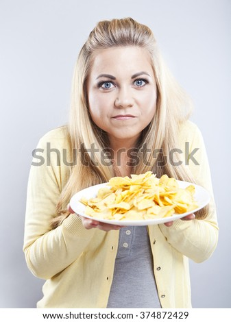 Young girl with potato chips. She thinks. Blonde watch your diet