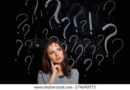 Young girl with question mark on a gray background - stock photo