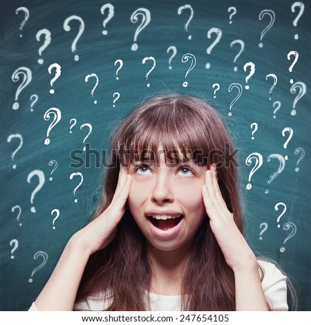 Young girl with questioning expression and question marks above her head and blackboard in the background  - stock photo