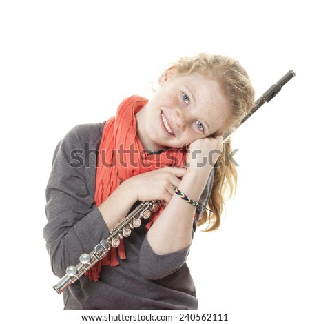 young girl with red hair and freckles with flute in studio against white background