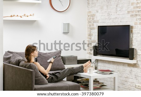 young girl with remote control in hand, sitting on a sofa and watches TV.