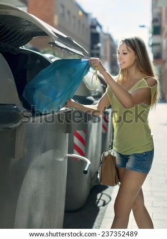 Young girl with rubbish near refuse collection container