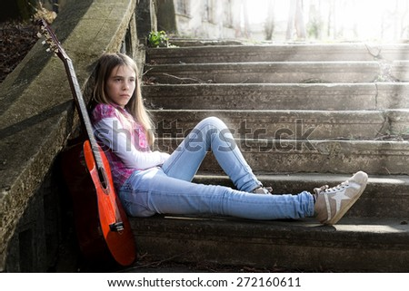 Young Girl With Sad Expression on Her Face Leaning on the Wall While Sun Rays Falling on Her - stock photo