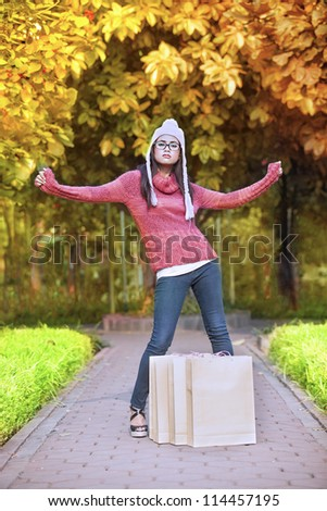 Young girl with shopping bag posing in autumn leaves. Shot outdoor during autumn