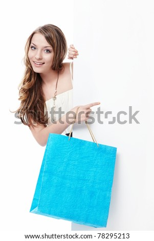 Young girl with shopping bags and empty the board on a white background - stock photo
