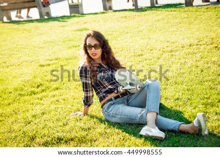 Young girl with skateboard. In the park