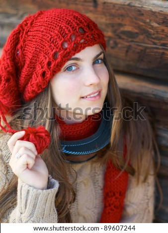 Young girl with ski mask and red hat and scarf against wooden wall. - stock photo
