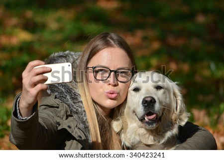 Young girl with spectacles posing and taking selfie with her golden retriever dog - stock photo