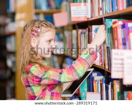 Young girl with tablet computer chooses a book in the library - stock photo