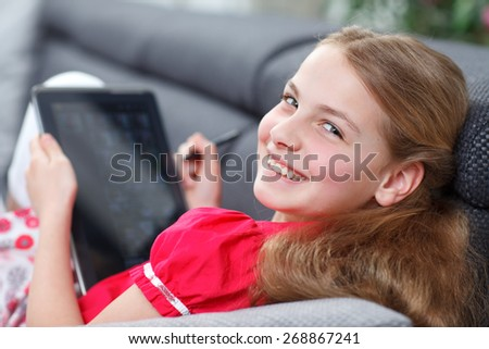 young girl with tablet lying on sofa and smiling - stock photo