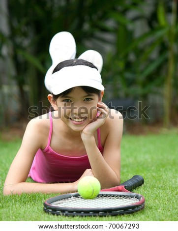 Young girl with tennis racket in outdoor park