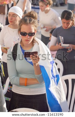 Young girl with the flag prays in the western wall of Jerusalem. - stock photo