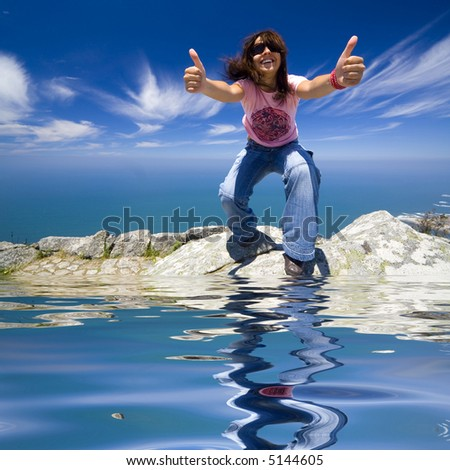 young girl with thumbs up in a beautiful landscape with blue water - stock photo