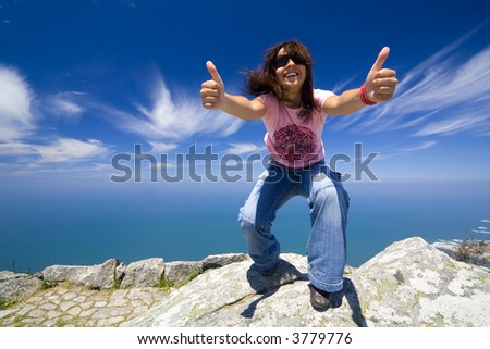 young girl with thumbs up in a beautifull landscape with blue water - stock photo