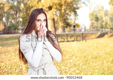 Young girl with tissue having flu or allergy, outdoor