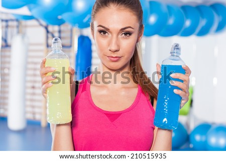 Young girl with two isotonic drink (yellow, blue), gym. She is considering which one to choose - stock photo