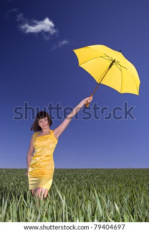 Young  girl with umbrella on a meadow.