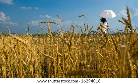 Young girl with umbrella walks on a field - stock photo