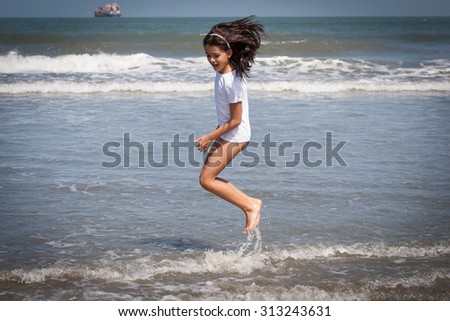 Young girl with white shirt jumps at seashore waves