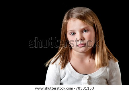Young girl with white sweater isolated on black with uninterested look - stock photo