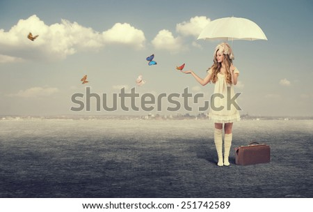 Young girl with white umbrella catches butterflies. - stock photo