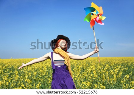 Young girl with wind turbine at rapeseed field.