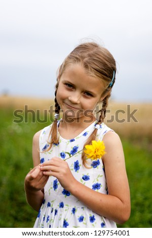 Young girl with yellow flower at country - stock photo