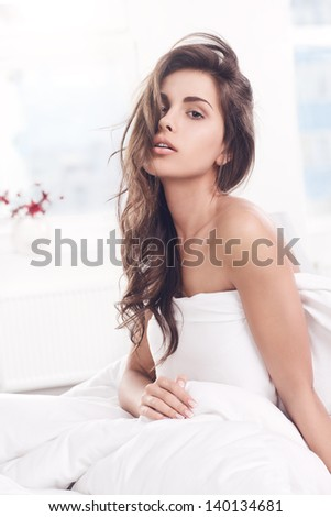 young girl woke up and sitting on a bed - stock photo