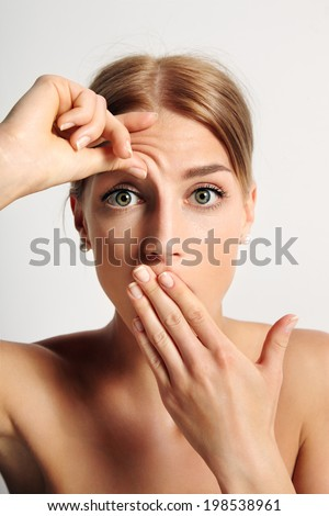 young girl wondering that she have first wrinkle on her forehead - stock photo