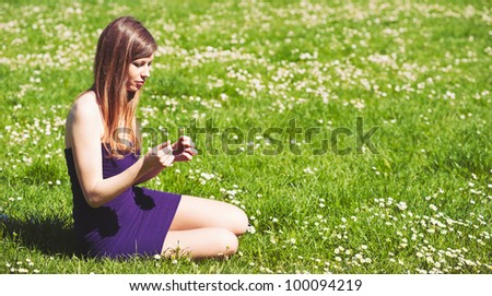 Young girl wonders on love with daisy flower. Room for text.