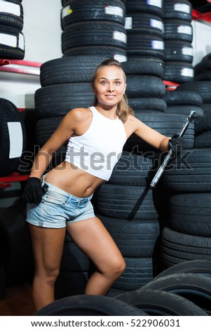 Young girl working in car workshop indoors