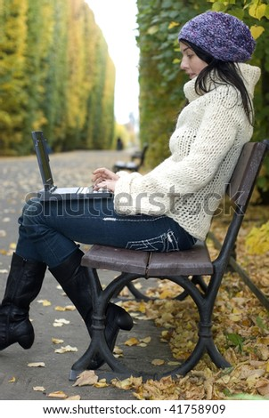 Young girl working on a laptop in an autumn park. - stock photo