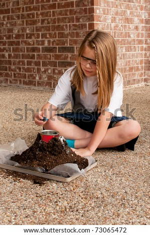 Young girl working on volcano type demonstration for school science project, adding food color - stock photo