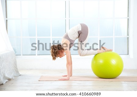 Young girl working out at the gym with a ball. Beautiful woman doing exercises with fitness ball at home.