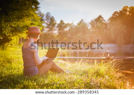 Young girl working/studing in the park at sunset time  - stock photo