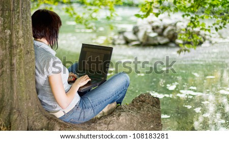 Young girl working with laptop under a tree, enjoying the nice weather in summertime. - stock photo