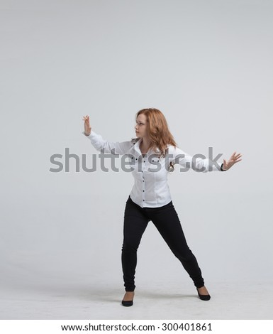 Young girl working with virtual screen on gray background - stock photo